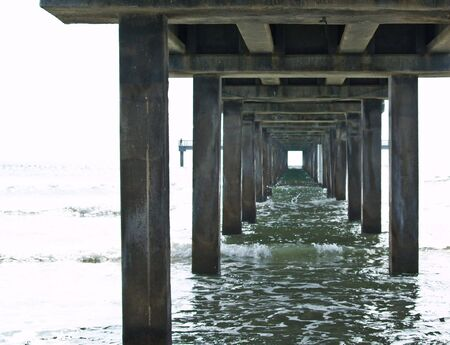 Shot taken under a pier showing the trestles converging in the distance.
