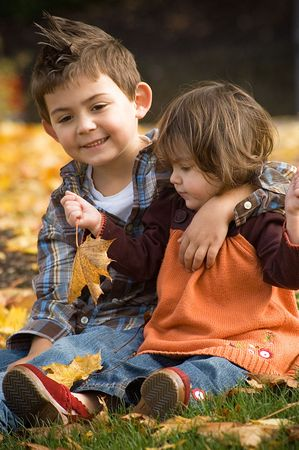 Young girl with her brother in an orange sweater and jeans playing in the fall leaves