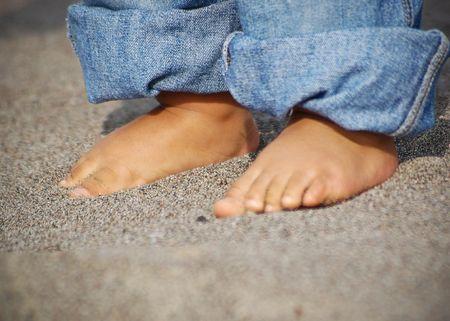 Colpo di piedi di un giovane ragazzo e arrotolato i jeans sotto la sabbia in spiaggia