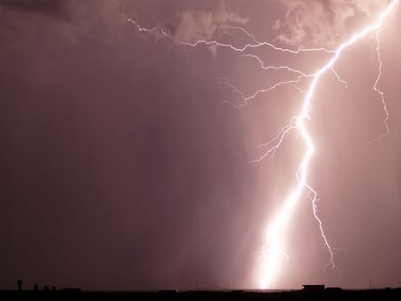 striking: Arc of lightning striking the ground against a night sky