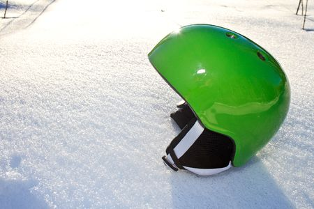 Bright green snowboarding helmet sitting on the snow on a sunny day photo