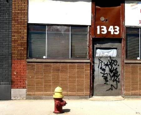 defaced: Yellow capped fire hydrant in front of an abandoned building