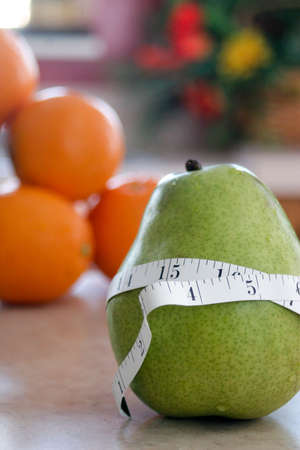 Green pear with a measuring tape around it with oranges in the background slightly blurred by depth of field photo