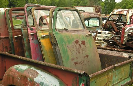 Old car doors in the back of a rusty pickup truck