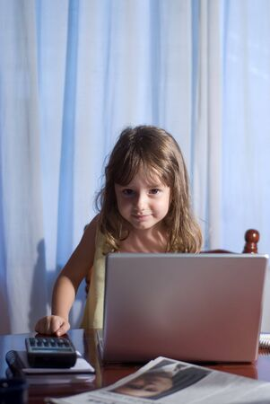 Little girl behind a laptop in a home office photo