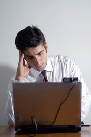 Man in a shirt and tie working late isolated against a white background photo