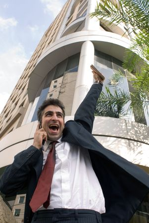 Man in a business suit on the phone pumping his fist in the air photo