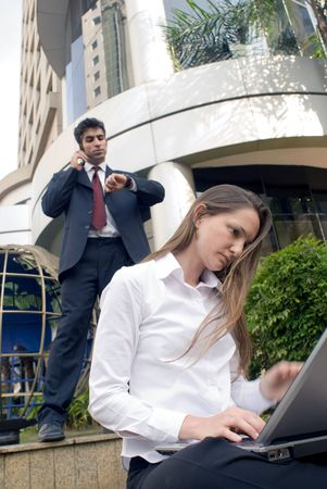 Man and woman in business attire working on a laptop and on the cell phone photo