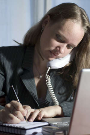 Woman seated at a desk taking notes while on the phone photo