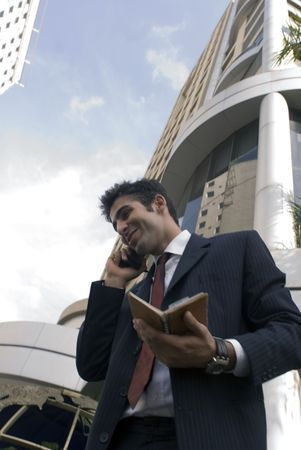 Business man smiling as he talks into the phone while holding his diary photo