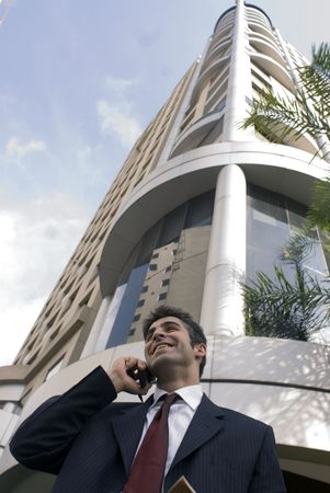 Man in a business suit on the phone smiling and chatting photo