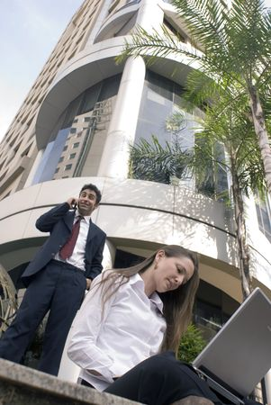 Man and woman in business attire working together outdoors photo