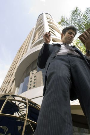 Business man checking out his schedule. Shot from a low camera angle looking up photo