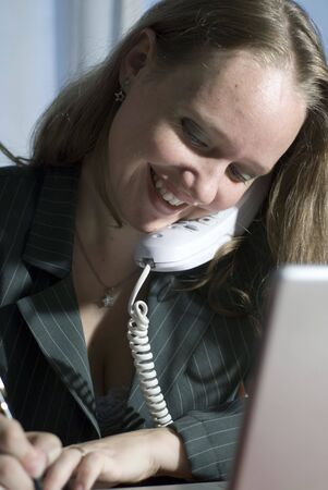 Woman in a business suit smiling while she is on the phone photo