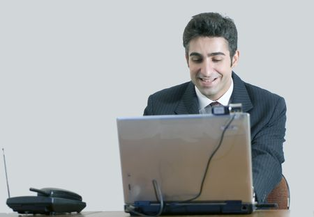 Business man working at his laptop and smiling. Isolated against a grey background photo