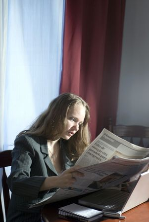 Woman in business attire reading the newspaper while seated at a desk photo