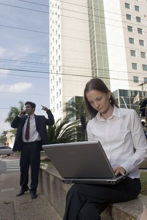 A man and a woman in business attire working on a laptop and cell phone Stock Photo - 2719903