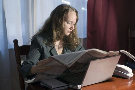 Horizontally framed shot of a woman in a business suit reading a newspaper photo