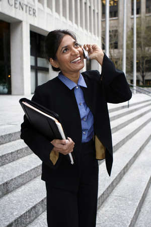 Exceutive Indian woman talking on a cellphone dressed in a black suit. Stock Photo - 2739750