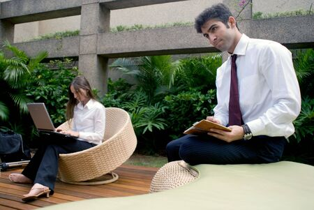 Man and woman in business attire working together on an outdoor patio Stock Photo