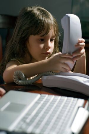 Young girl on the phone in a home office Stock Photo
