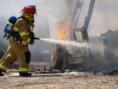 Shot of a firefighter putting out a burning RV.
