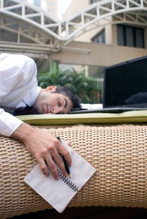 Passed out: Man in business attire passed out in front of his laptop