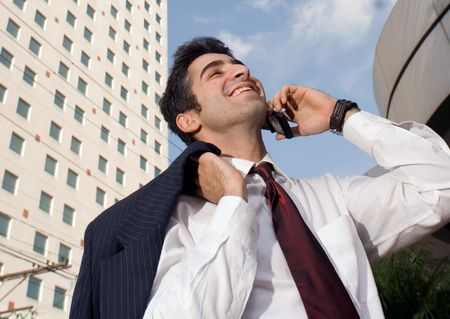 Man with his jacket over his shoulder smiling while talking on the phone Stock Photo