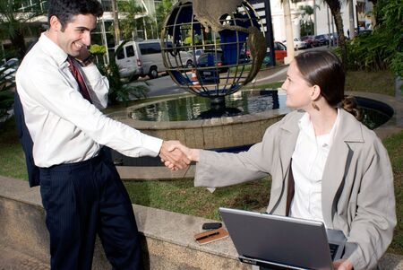 Male and female colleagues shaking hands while working outdoors Stock Photo - 2738655