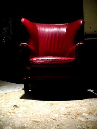 Shot of sole red leather chair under a light.