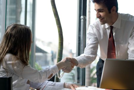 Male and female business people shaking hands over a deal photo
