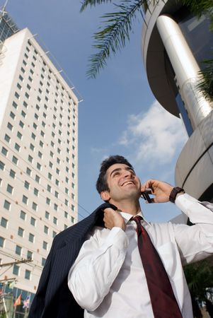 Man smiling while on the phone with his jacket over his shoulder Stock Photo - 2740043