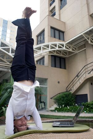 Woman in business attire doing a headstand to clear her head photo