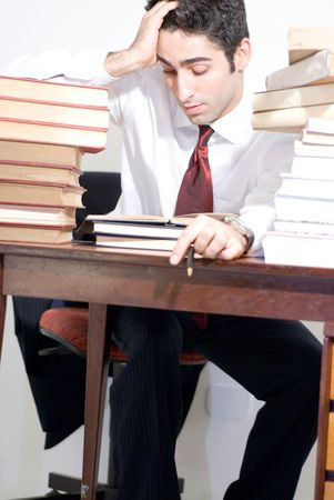 Man in business attire surrounded by books photo