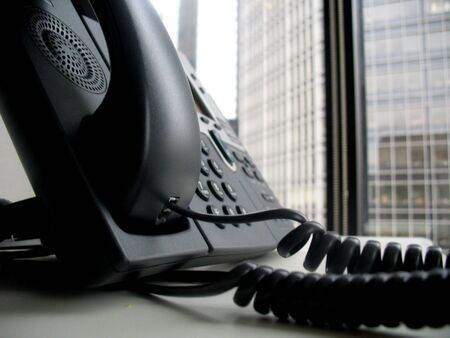 handset: Shot of a business telephone handset on a desk. Stock Photo