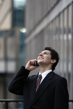 Business man leaning back and laughing heartily while on his cell phone photo