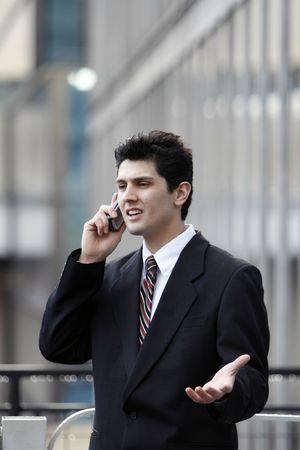 quizzical: Hombre de negocios insinuar mientras habla por su tel�fono celular al aire libre  Foto de archivo