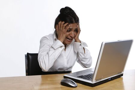 Indian woman at her laptop holding her head in anguish photo