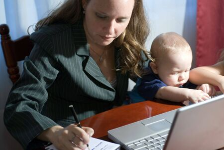 telework: A businesswoman working from home sitting next to her son and daughter.