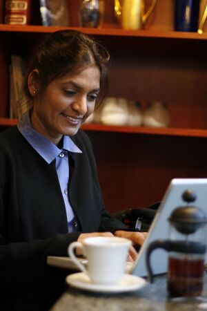 Vertical shot of an Indian business woman in a business suit working in a cafe Stock Photo