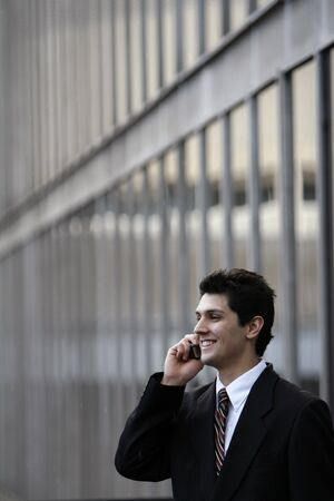 Male caucasian business man smiling while talking on his cell phone while standing outside an office building in the rain
