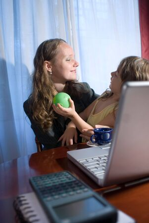 homeoffice: A mother and her daughter playing in front of a laptop, while taking a break.