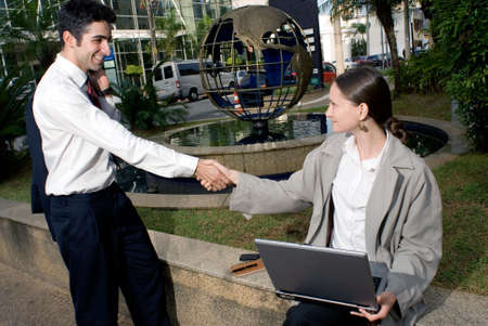 Businessman and woman shaking hands, in front of a globe sculpture. Banco de Imagens - 2831182