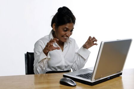East Indian business woman making faces at her laptop isolated against a white background photo