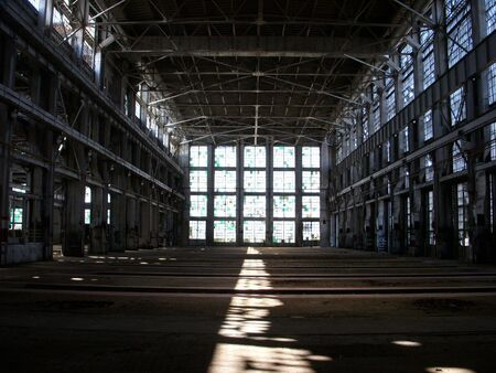 abandoned factory: A shot of a wide open industrial shop, with light streaming in from a wall of windows at the far point.