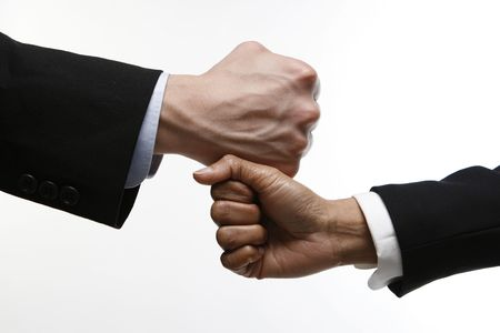 Two fists, one on top of the other. One belongs to a caucasian male the other belongs to an Indian woman Stock Photo