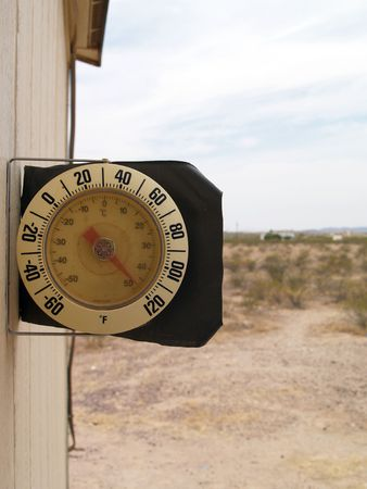 Round dial thermometer showing 120 degrees on a warm day in the desert Banco de Imagens