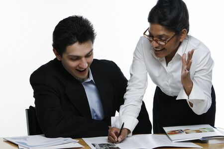 reviewing: Male and female business colleagues with mouths open in excitement reviewing a document together