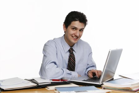 Business man sitting at his desk, working on a laptop and smiling at the camera Stock Photo - 2870291