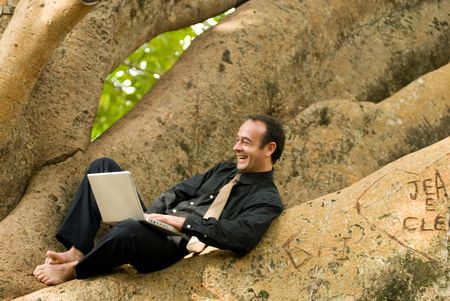 Latin american businessman working on a laptop while sitting outdoors in a tree